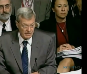 Former WellPoint VP Elizabeth Fowler sits behind her boss, Sen. Max Baucus, as he announces in 2009 that the health care bill will have no public option. Photograph: screen grab, Bill Moyers' Journal
