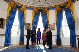 U.S President Barack Obama takes the oath of office from U.S. Supreme Court Chief Justice John Roberts as first lady Michelle Obama holds the bible and their daughters Malia and Sasha look on in the Blue Room of the White House in Washington